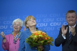 German Chancellor and Christian Democratic Union CDU chancellor candidate Angela Merkel (C) holds flowers while being applauded by Christian social union CSU parliamentary group leader Gerda Hasselfeldt (L) and CDU General secretary Hermann Groehe after the first exit polls results were released at the CDU headquarters in Berlin, on September 22,  2013, the day of the German general elections. AFP PHOTO / JOHANNES EISELE