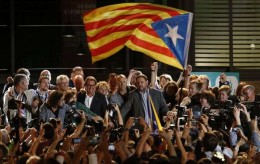 """A """"Estelada"""" or pro independence flags is waved in front of the President of Democratic Convergence of Catalonia Artur Mas, left and Oriol Junqueras, president of the Esquerra Republicana de Catalunya party in front of supporters in Barcelona, Spain, Sunday Sept. 27, 2015. Voters in Catalonia participated in an election Sunday that could propel the northeastern region toward independence from the rest of Spain or quell secessionism for years. An exit poll predicts that pro-independence parties in Spain's Catalonia region are likely to win a majority of seats in the regional parliament, but it's unclear whether they would be able to come together to push together on a plan to secede from Spain. (AP Photo/Manu Fernandez) Spain Catalonia Independence"""